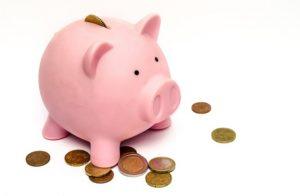 豚の貯金箱と転がっている小銭の写真です
