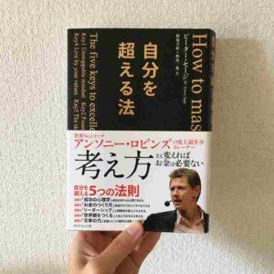 自分を超える法の本を持つ手